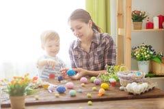 Preparações da Páscoa Mãe nova feliz que passa o tempo com seu filho alegre Ovos da páscoa felizes da pintura da mamã da família  imagem de stock royalty free