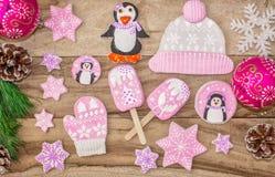 Preparações do Natal Pão-de-espécie, pinguins, mitenes e chapéus com asteriscos, gelado, em um fundo de madeira imagem de stock royalty free