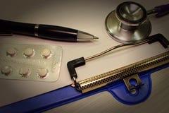 Preparações medicinais, instrumentos, um estetoscópio, um dobrador, uma pena, fotografia de stock