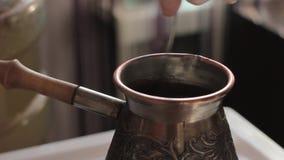 Prepara el café turco tradicional en el pote de cobre sobre estufa almacen de metraje de vídeo