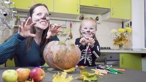 Prepara??es de Dia das Bruxas A mamã e a filha estão jogando na composição Abóbora da mostra filme