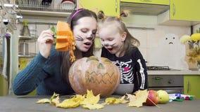 Prepara??es de Dia das Bruxas A mamã e a filha estão jogando na composição Corte a ab?bora filme