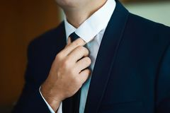 Prepara la preparación de la mañana, novio hermoso que consigue vestido y que se prepara para la boda, tenencia un lazo en sus ma fotografía de archivo