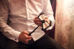 Prepara??o da manh? dos noivos, noivo consider?vel que obt?m vestido foto de stock