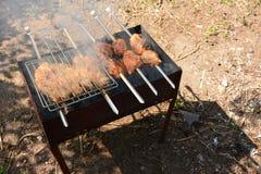 Preparación, cocinando kebabs en el carbón de leña al aire libre Fotos de archivo libres de regalías