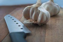 Preparación de alimento biológico, cocinando concepto: cabezas crudas de los bulbos del ajo, cuchillo en un fondo de madera rústi Foto de archivo libre de regalías