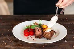 Preparación de alimento El jefe añade la salsa a la carne fotografía de archivo libre de regalías