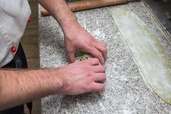 Preparación de espaguetis primer de los cocineros de las manos fotos de archivo