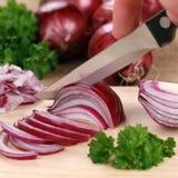 Preparación de la comida: cortar una cebolla roja Imagen de archivo libre de regalías