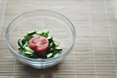 Preparación de la ensalada vegetariana, de un cuenco de verduras tomate y del pepino imagenes de archivo