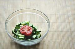 Preparación de la ensalada vegetariana, de un cuenco de verduras tomate y del pepino fotografía de archivo