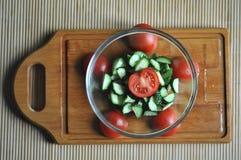 Preparación de la ensalada vegetariana, de un cuenco de verduras tomate y del pepino, visión superior imágenes de archivo libres de regalías