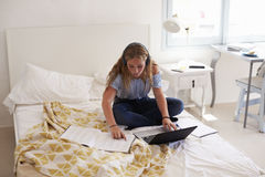 Preparación de la lectura del adolescente que se sienta en su cama con el ordenador portátil Foto de archivo