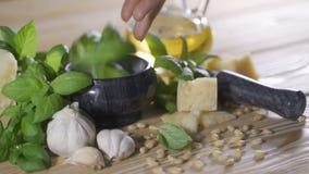 Preparación de la salsa del pesto de la albahaca, del queso parmesano, del aceite de oliva y del ajo frescos con una licuadora almacen de video