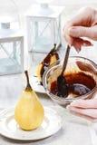 Preparación de las peras con el chocolate Imagenes de archivo