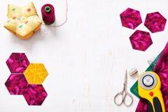 Preparación de los pedazos del hexágono de tela para coser un edredón Grandmother& x27; jardín de flores de s Foto de archivo libre de regalías