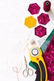 Preparación de los pedazos del hexágono de tela para coser un edredón Grandmother& x27; jardín de flores de s Foto de archivo