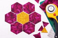Preparación de los pedazos del hexágono de tela para coser un jardín de flores del ` s de la abuela del edredón Foto de archivo