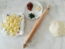 Preparación de los platos con las patatas y la especia verde Fotos de archivo