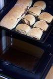 Preparación de los rollos de canela El molde para el horno sacado del horno Hay bollos listos y un rollo con canela en él Imagenes de archivo
