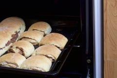 Preparación de los rollos de canela El molde para el horno sacado del horno Hay bollos listos y un rollo con canela en él Foto de archivo libre de regalías