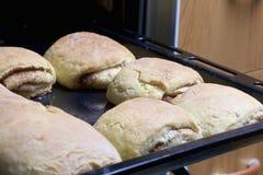 Preparación de los rollos de canela El molde para el horno sacado del horno Hay bollos listos y un rollo con canela en él Fotografía de archivo libre de regalías