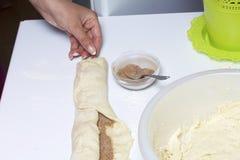 Preparación de los rollos de canela La mujer apaga la pasta con un relleno del canela y del azúcar Imagen de archivo