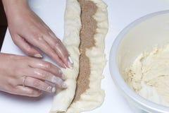 Preparación de los rollos de canela La mujer apaga la pasta con un relleno del canela y del azúcar Fotografía de archivo