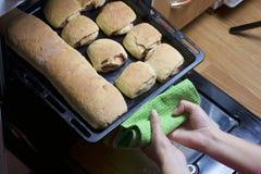Preparación de los rollos de canela La mujer saca un molde para el horno del horno Hay bollos listos y un rollo con canela en él Imagen de archivo