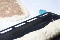 Preparación de los rollos de canela La ruleta está mintiendo en la bandeja de la hornada Al lado de ella miente la pasta rodada c Foto de archivo libre de regalías