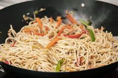 Preparación de los tallarines chinos en un wok Imágenes de archivo libres de regalías