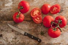 Preparación de los tomates frescos para una ensalada o el cocinar Imagenes de archivo