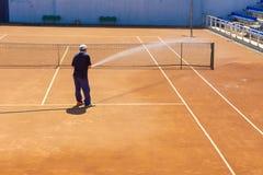 Preparación de un campo de tenis que riega de una manguera Un hombre que riega un campo de tenis Fotos de archivo libres de regalías