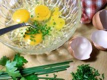 Preparación de un omlet con las cebolletas y el perejil Fotos de archivo libres de regalías