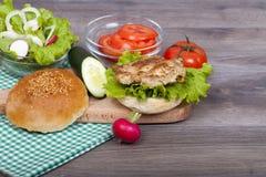 Preparación de una hamburguesa muy sabrosa del pollo con la ensalada fresca Fotografía de archivo libre de regalías