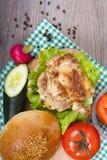 Preparación de una hamburguesa muy sabrosa del pollo con lechuga, el tomate y c Fotografía de archivo libre de regalías