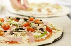 Preparación de una pizza Imagenes de archivo