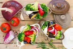 Preparación del adorno Verduras frescas crudas - bróculi, berenjena, pimientas, tomates, cebollas, ajo en potes de la porción Imagen de archivo libre de regalías