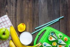 Preparación del almuerzo rápido para el alumno Bocadillos divertidos, leche, frutas en copyspace de madera oscuro de la opinión s Imagen de archivo libre de regalías