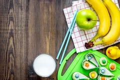 Preparación del almuerzo rápido para el alumno Bocadillos divertidos, leche, frutas en copyspace de madera oscuro de la opinión s Foto de archivo
