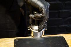 Preparación del café: machacamiento y la tableta presionada Temperas en el tenedor Superficie de madera espresso Barista del trab fotos de archivo