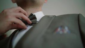 Preparación del hombre o del novio de negocios con un traje gris Y ajuste la corbata de lazo Cierre para arriba metrajes