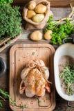 Preparación del pollo asado con las hierbas y las verduras Foto de archivo