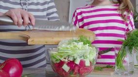 Preparación del primer de la ensalada Manos de la abuela y de la nieta 4K almacen de metraje de vídeo