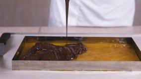 Preparación del relleno para los dulces El chocolate líquido se vierte en la mermelada del albaricoque almacen de metraje de vídeo