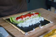 Preparación del sushi hecho en casa con el arroz blanco, el atún, los tomates y la ensalada en una hoja de alga marina secada del foto de archivo libre de regalías