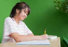 Preparación joven asiática de la escritura de la muchacha del adolescente en la etiqueta de la biblioteca escolar Imagen de archivo libre de regalías