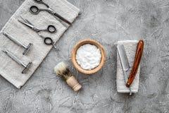 Preparación para afeitar de los hombres Brocha de afeitar, maquinilla de afeitar, espuma, sciccors en copyspace de piedra gris de Foto de archivo