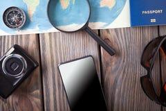 Preparación para el concepto que viaja, pasaporte, smartphone, cámara, mapa en un fondo de madera Fotos de archivo libres de regalías