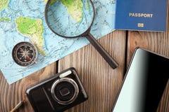 Preparación para el concepto que viaja, pasaporte, smartphone, cámara, mapa en un fondo de madera Fotografía de archivo libre de regalías
